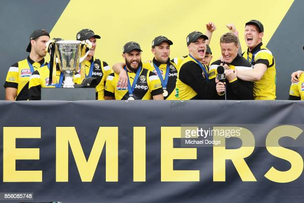 Dustin Martin of the Tigers and Jack Riewoldt hug Tigers head coach Damien Hardwick as players celebrate winning yesterday's AFL Grand Final at Punt...
