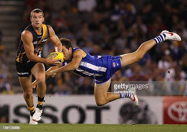Dustin Martin of the Tigers breaks past a tackle by Levi Greenwood of the Kangaroos during the round one NAB Cup AFL match between the Richmond...