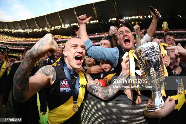 Dustin Martin of the Tigers celebrates victory with the Premiership Trophy and fans during the 2019 AFL Grand Final match between the Richmond Tigers...