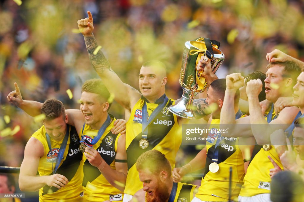 Dustin Martin of the Tigers celebrates with the AFL Premiership Cup on stage as confetti flies in the air after winning the 2017 Toyota AFL Grand Final match between the Adelaide Crows and the Richmond Tigers at the Melbourne Cricket Ground on September 30, 2017 in Melbourne, Australia.