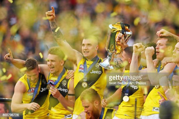 Dustin Martin of the Tigers celebrates with the AFL Premiership Cup on stage as confetti flies in the air after winning the 2017 Toyota AFL Grand...