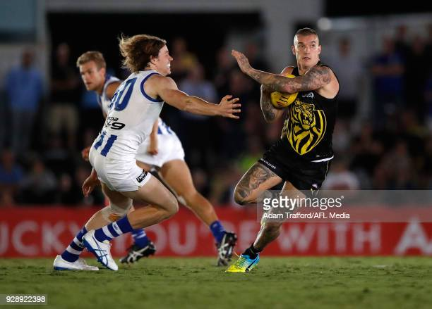 Dustin Martin of the Tigers evades Ben Brown of the Kangaroos during the AFL 2018 JLT Community Series match between the Richmond Tigers and the...