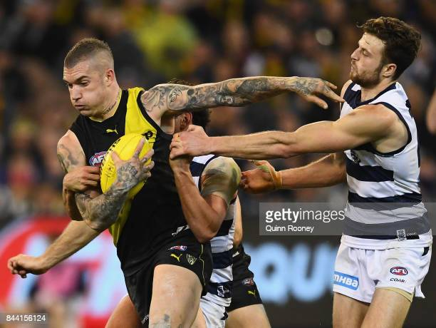 Dustin Martin of the Tigers fends off a tackle by Jordan Murdoch of the Cats during the AFL Second Qualifying Final Match between the Geelong Cats...