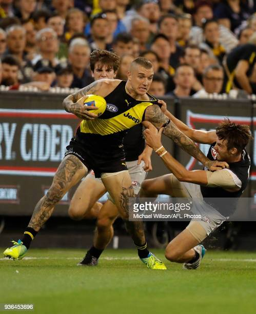Dustin Martin of the Tigers fends off Dale Thomas of the Blues during the 2018 AFL round 01 match between the Richmond Tigers and the Carlton Blues...