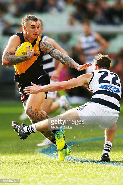 Dustin Martin of the Tigers fends off Mitch Duncan of the Cats who tries to trip with with a leg during the round 21 AFL match between the Richmond...