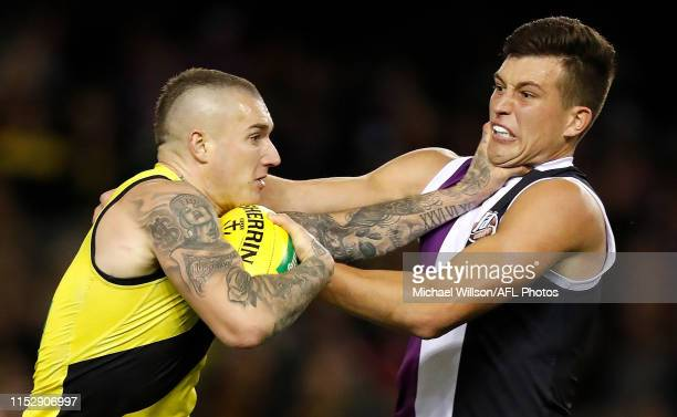 Dustin Martin of the Tigers fends off Rowan Marshall of the Saints during the 2019 AFL round 15 match between the St Kilda Saints and the Richmond...
