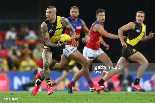 Dustin Martin of the Tigers handballs during the round 10 AFL match between the Richmond Tigers and the Brisbane Lions at Metricon Stadium on August...