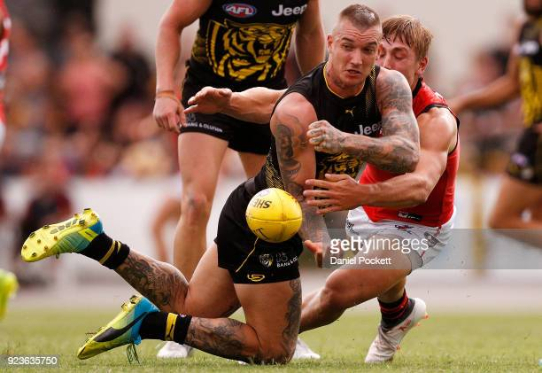 Dustin Martin of the Tigers handpasses the ball under pressure during the JLT Community Series AFL match between the Essendon Bombers and the...