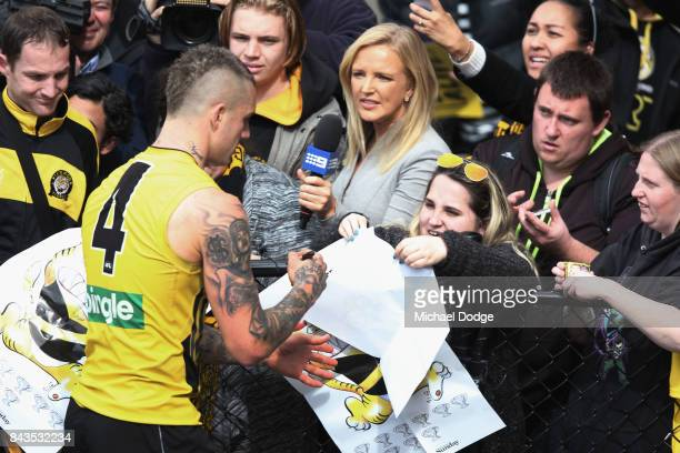 Dustin Martin of the Tigers is asked questions by a media reporter as he signs autographs for fans during a Richmond Tigers AFL training session at...