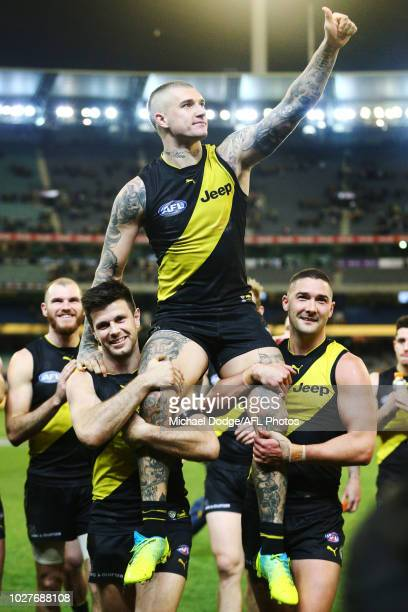 Dustin Martin of the Tigers is carried off after winning his 200th match by Trent Cotchin of the Tigers and Shaun Grigg of the Tigers during the AFL...