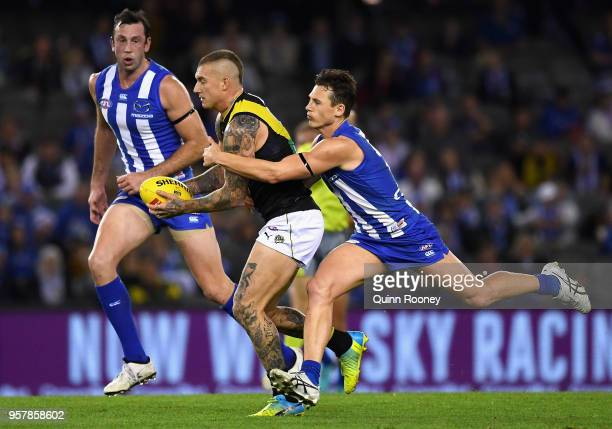 Dustin Martin of the Tigers is tackled by Ben Jacobs of the Kangaroos during the round eight AFL match between the North Melbourne Kangaroos and the...