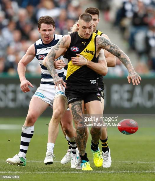 Dustin Martin of the Tigers is tackled by Cameron Guthrie of the Cats ahead of Patrick Dangerfield of the Cats and Trent Cotchin of the Tigers during...