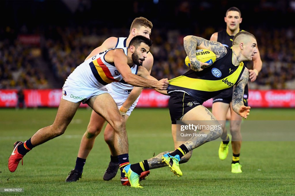 Dustin Martin of the Tigers is tackled by Wayne Milera of the Crows during the round 16 AFL match between the Richmond Tigers and the Adelaide Crows at Melbourne Cricket Ground on July 6, 2018 in Melbourne, Australia.