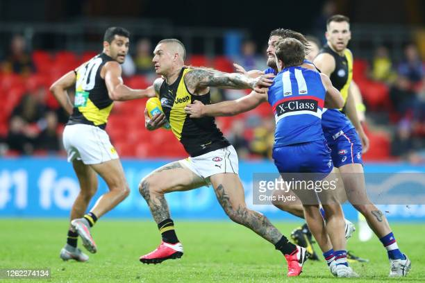 Dustin Martin of the Tigers is tackled during the round nine AFL match between the Western Bulldogs and the Richmond Tigers at Metricon Stadium on...