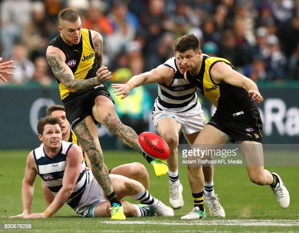 Dustin Martin of the Tigers kicks the ball out of the middle ahead of Trent Cotchin of the Tigers and Patrick Dangerfield and Scott Selwood of the...