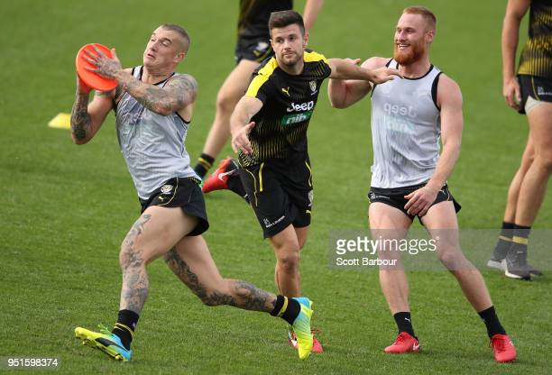 Dustin Martin of the Tigers runs as Trent Cotchin of the Tigers and Nick Vlastuin of the Tigers look on as they play a game with a frisbee during the...