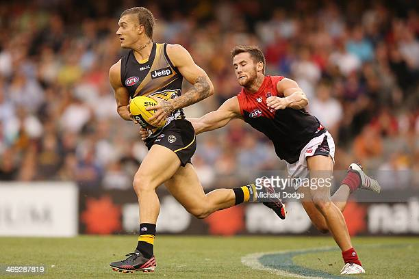 Dustin Martin of the Tigers runs past Jeremy Howe of the Demons during the round one AFL NAB Challenge Cup match between the Richmond Tigers and the...