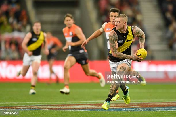 Dustin Martin of the Tigers runs with the ball during the round 17 AFL match between the Greater Western Sydney Giants and the Richmond Tigers at...