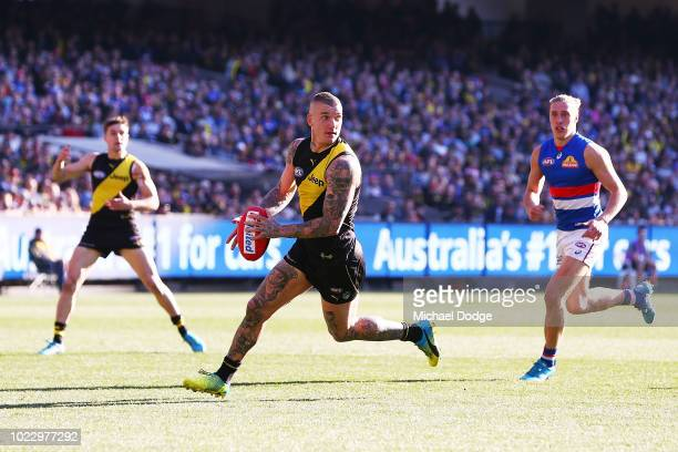 Dustin Martin of the Tigers runs with the ball during the round 23 AFL match between the Richmond Tigers and the Western Bulldogs at Melbourne...