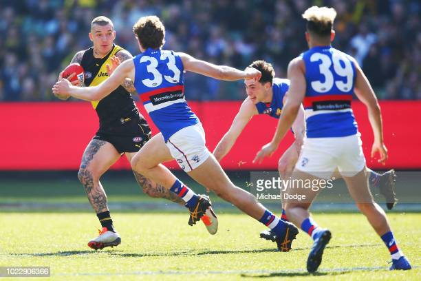 Dustin Martin of the Tigers runs with the ball from Aaron Naughton of the Bulldogs during the round 23 AFL match between the Richmond Tigers and the...