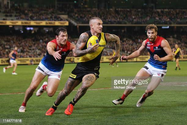 Dustin Martin of the Tigers runs with the ball from Michael Hibberd and Jack Viney of the Demons during the round 6 AFL match between Richmond and...
