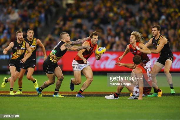 Dustin Martin of the Tigers tackles Jobe Watson of the Bombers during the round 10 AFL match between the Richmond Tigers and the Essendon Bombers at...