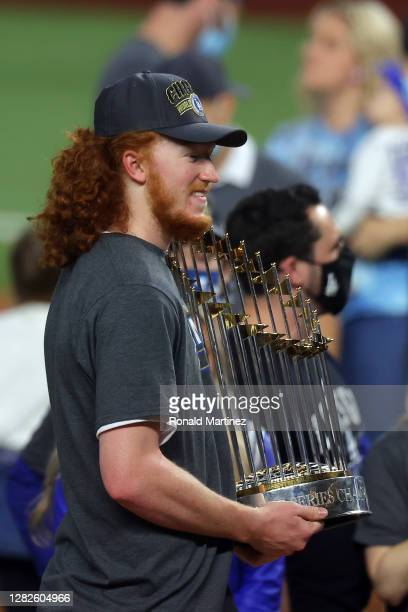 Dustin May of the Los Angeles Dodgers celebrates with the Commissioners Trophy after defeating the Tampa Bay Rays 31 in Game Six to win the 2020 MLB...