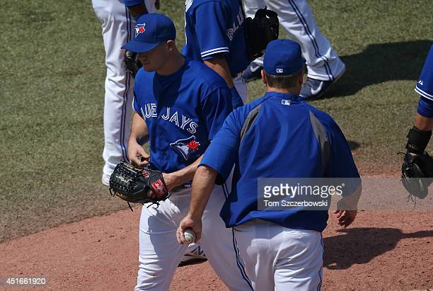 Dustin McGowan of the Toronto Blue Jays exits the game as he is relieved by manager John Gibbons in the eighth inning during MLB game action against...