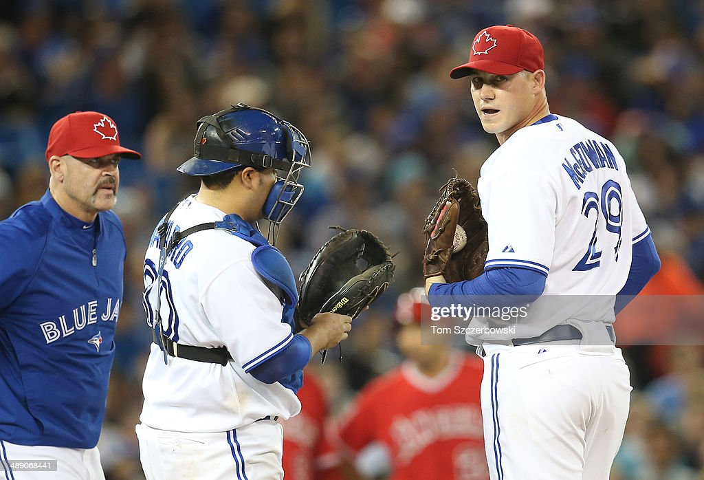 Dustin McGowan #29 of the Toronto Blue Jays is visited by pitching coach Pete Walker #40 and catcher Dioner Navarro #30 in the fifth inning during MLB game action against the Los Angeles Angels of Anaheim on May 9, 2014 at Rogers Centre in Toronto, Ontario, Canada.
