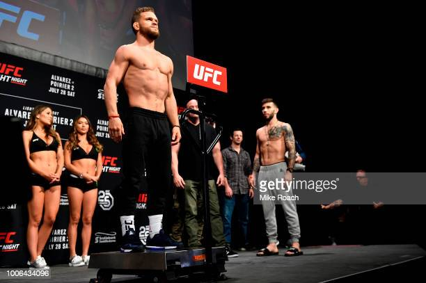 Dustin Ortiz poses on the scale as opponent Matheus Nicolau of Brazil waits on stage during the UFC Fight Night weighin at Scotiabank Saddledome on...