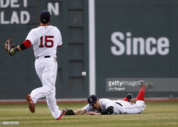 Dustin Pedroia and Grady Sizemore of the Boston Red Sox are unable to field a fly ball against the Texas Rangers in the 3rd inning against the Boston...