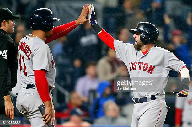 Dustin Pedroia and pinch runner Marco Hernandez of the Boston Red Sox celebrate after both scored in the eighth inning against the New York Yankees...