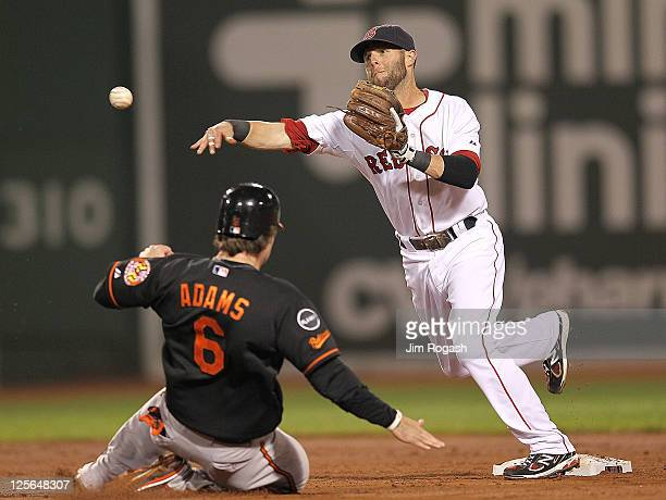 Dustin Pedroia of the Boston Red Sox attempts to turn a double play as Ryan Adams of the Baltimore Orioles slides in the second game of a...