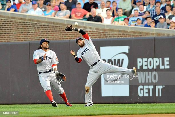 Dustin Pedroia of the Boston Red Sox can't make a catch against the Chicago Cubs as Darnell McDonald backs him up in the third inning on June 17 2012...