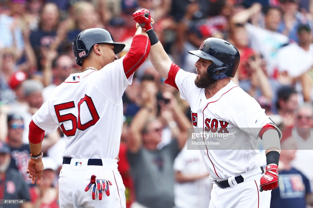 Dustin Pedroia #15 of the Boston Red Sox celebrates with Mookie Betts #50 after hitting a three run homer against the Toronto Blue Jays during the seventh inning at Fenway Park on July 20, 2017 in Boston, Massachusetts.