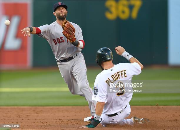 Dustin Pedroia of the Boston Red Sox completes the doubleplay by getting his throw off over the top of Trevor Plouffe of the Oakland Athletics in the...
