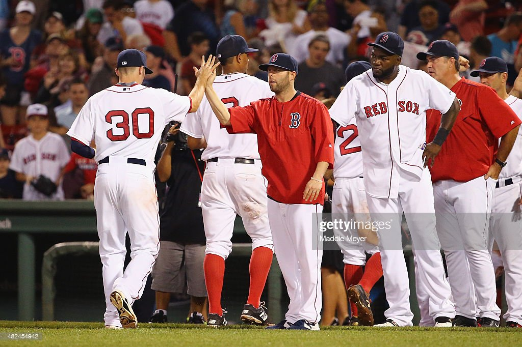 Dustin Pedroia #15 of the Boston Red Sox congratulates Josh Rutledge #30 after their 8-2 win over the Chicago White Sox at Fenway Park on July 30, 2015 in Boston, Massachusetts.