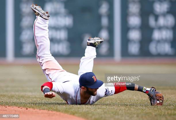 Dustin Pedroia of the Boston Red Sox dives for a ground ball against the Milwaukee Brewers during the Opening Day game at Fenway Park on April 4 2014...