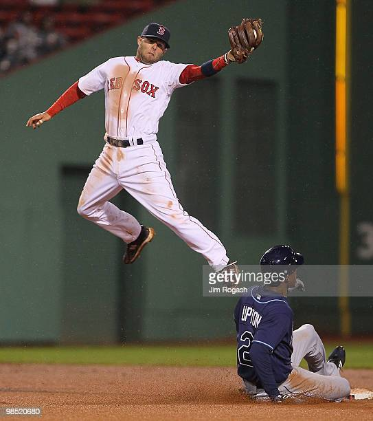 Dustin Pedroia of the Boston Red Sox fields a high throw as BJ Upton of the Tampa Bay Rays steals second base at Fenway Park on April 17 2010 in...