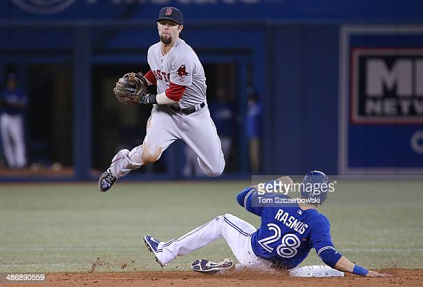 Dustin Pedroia of the Boston Red Sox forces out Colby Rasmus of the Toronto Blue Jays at second base in the eighth inning during MLB game action on...