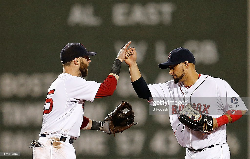 Dustin Pedroia #15 of the Boston Red Sox greets Shane Victorino #18 to celebrate a win over the Tampa Bay Rays at Fenway Park on July 23, 2013 in Boston, Massachusetts.