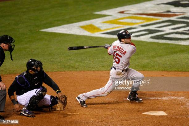Dustin Pedroia of the Boston Red Sox hits a two RBI double against the Colorado Rockies during Game 3 of the Major League Baseball World Series at...