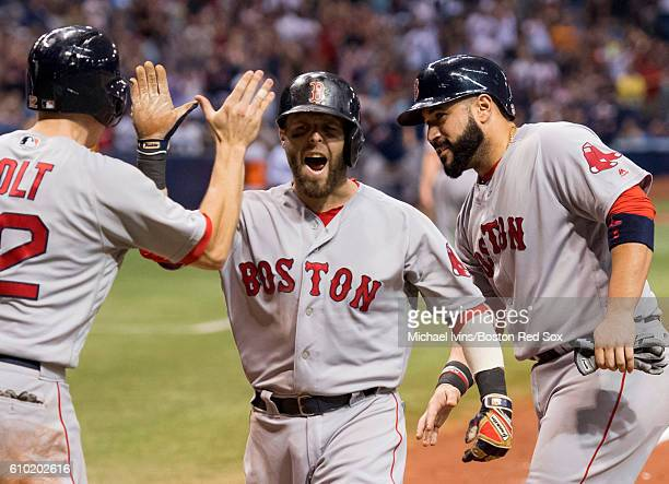 Dustin Pedroia of the Boston Red Sox is congratulated by Sandy Leon and Brock Holt after a grand slam against the Tampa Bay Rays in the seventh...
