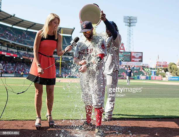 Dustin Pedroia of the Boston Red Sox is doused with Body Armor by Hanley Ramirez while speaking to the NESN reporter Guerin Austin after Pedroia hit...