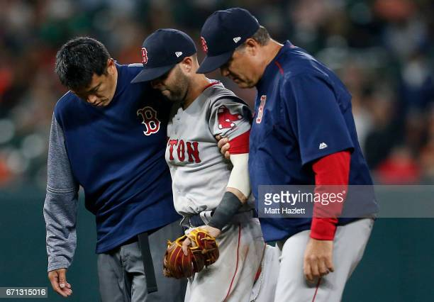 Dustin Pedroia of the Boston Red Sox is helped off of the field after colliding with Manny Machado of the Baltimore Orioles in the eighth inning at...