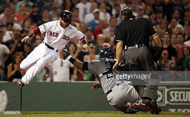 Dustin Pedroia of the Boston Red Sox is tagged out at home by Jose Molina of the Tampa Bay Rays in the sixth inning at Fenway Park on May 26 2012 in...