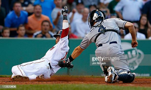 Dustin Pedroia of the Boston Red Sox is tagged out by Nick Hundley of the San Diego Padres in the 2nd inning trying to score at Fenway Park on July 2...
