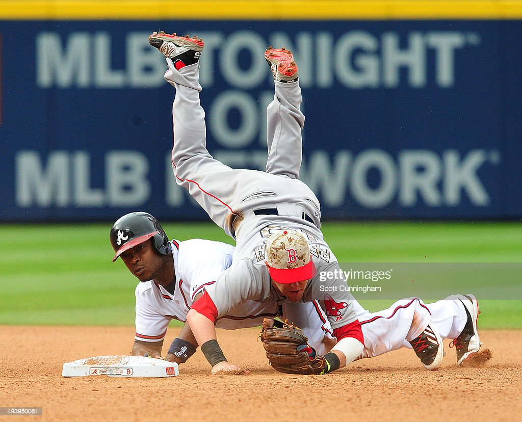 Dustin Pedroia #15 of the Boston Red Sox is upended after turning a 6th inning double play against Justin Upton #8 of the Atlanta Braves at Turner Field on May 26, 2014 in Atlanta, Georgia.