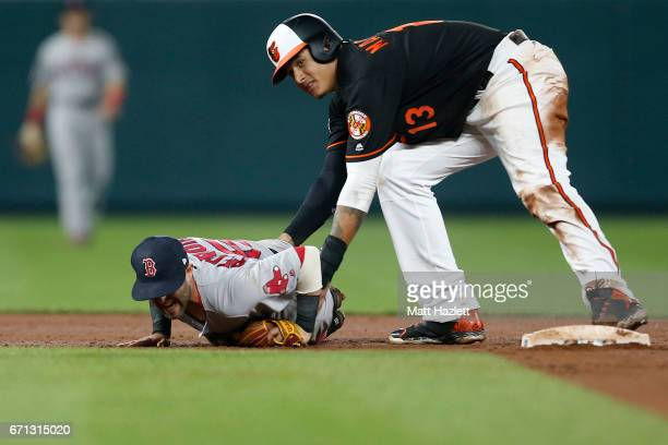Dustin Pedroia of the Boston Red Sox lays injured on the field after colliding at second base with Manny Machado of the Baltimore Orioles in the...