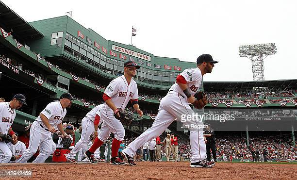 Dustin Pedroia of the Boston Red Sox leads his team onto the field against Tampa Bay Rays at Fenway Park April 15 2012 in Boston Massachusetts Both...